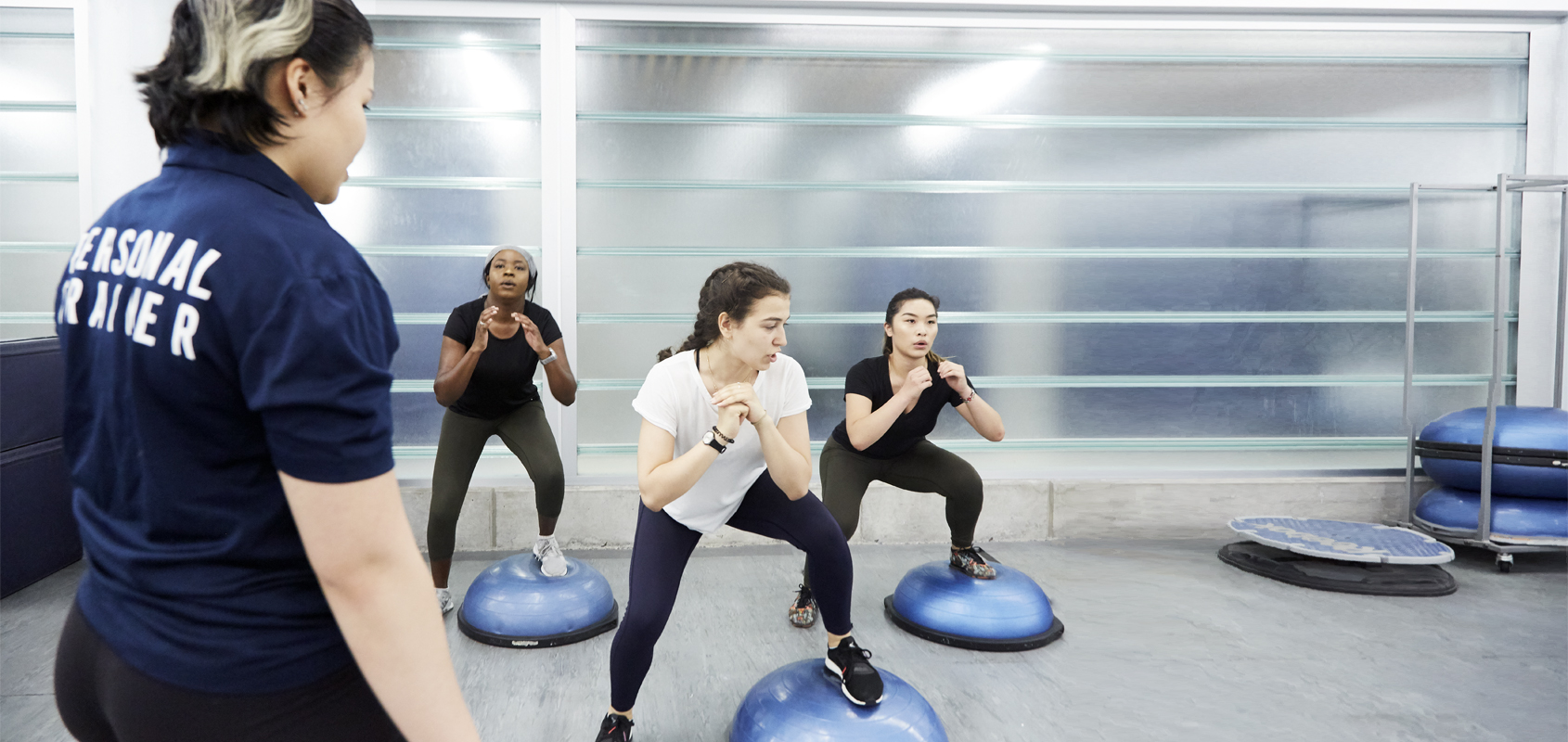 Three woman exercise with a personal trainer