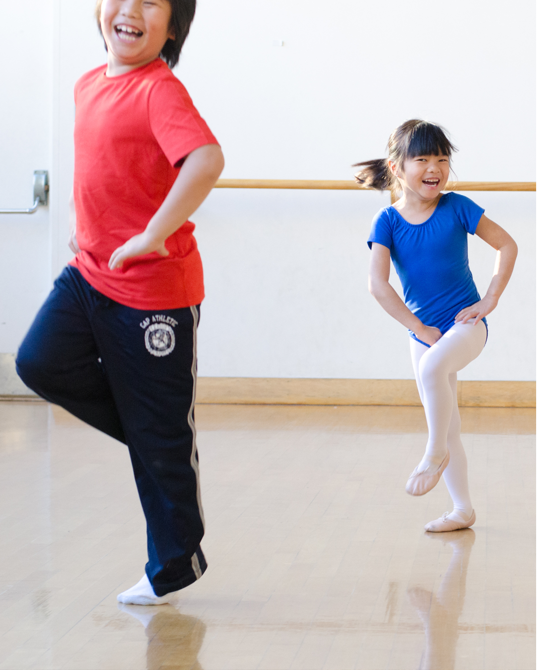two Asian children dancing in gym