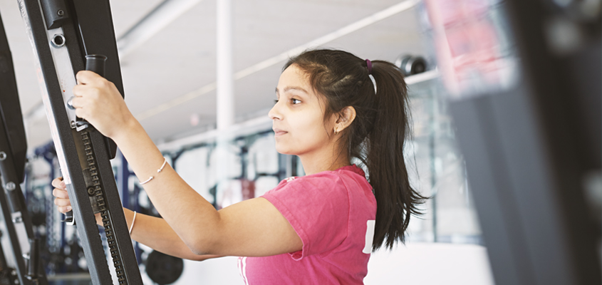 Female student using exercise machine