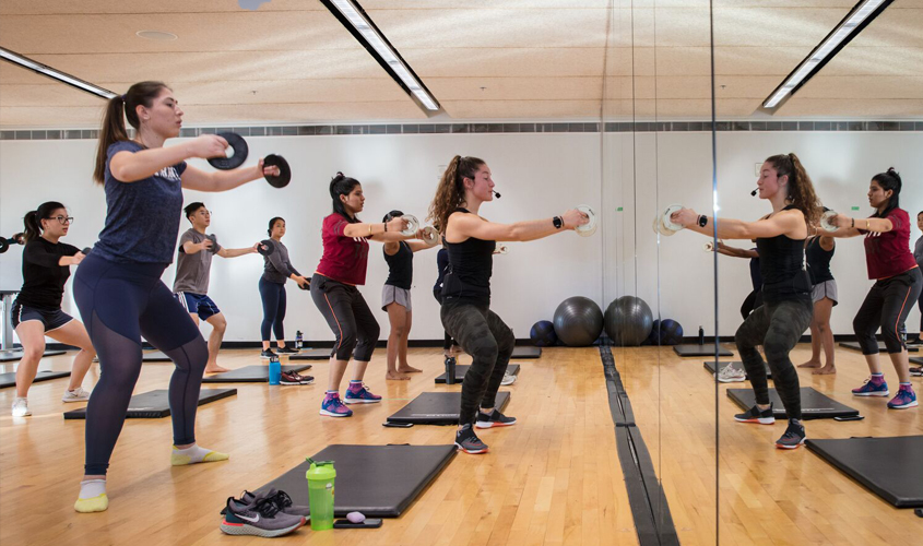 mixed group of students in barre class led by female fitness coach