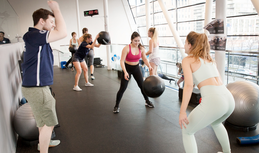 two young women conduct HIIT exercises under supervision of fitness coach