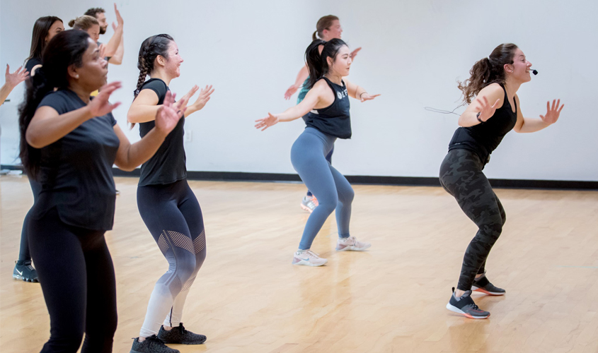 female coach leads class in cardio dance session