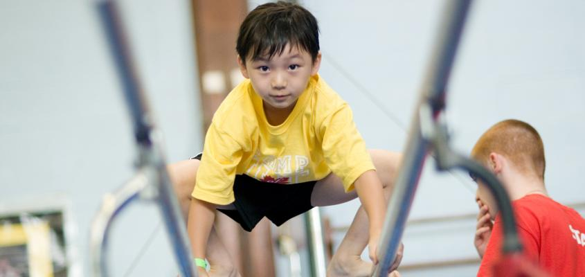 A young boy on the parallel bars