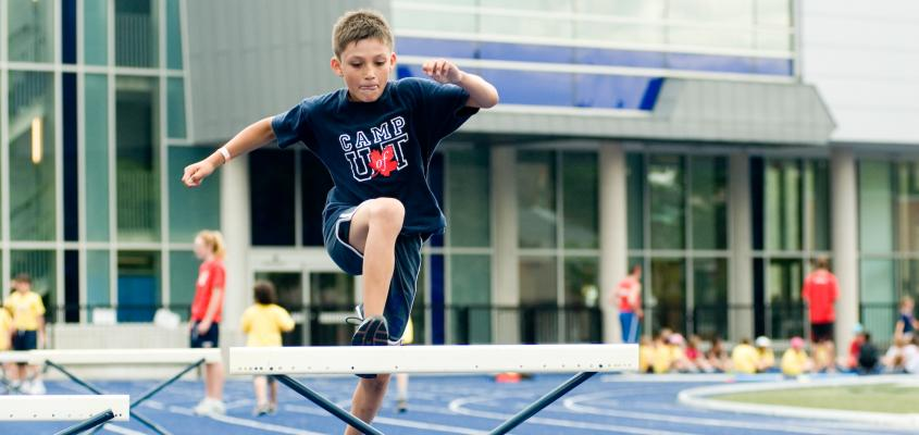 A young boy jumping over a hurdle