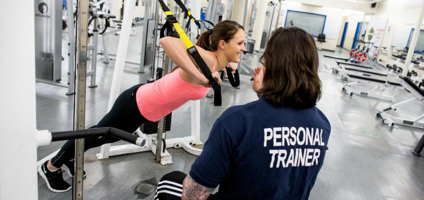 A personal trainer coaches a young woman