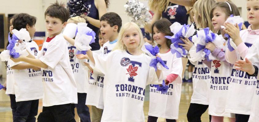 Children cheering at a Varsity Blues game