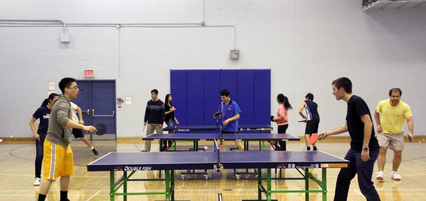 a group of men and women playing table tennis