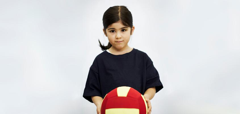 female child holding volleyball