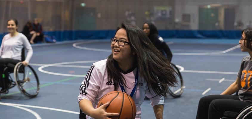Woman smiling playing wheelchair basketball
