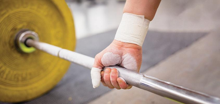 close up of hand gripping barbell