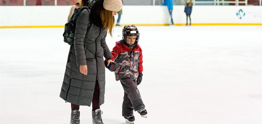 mother holds child's hand as they ice skate at rink