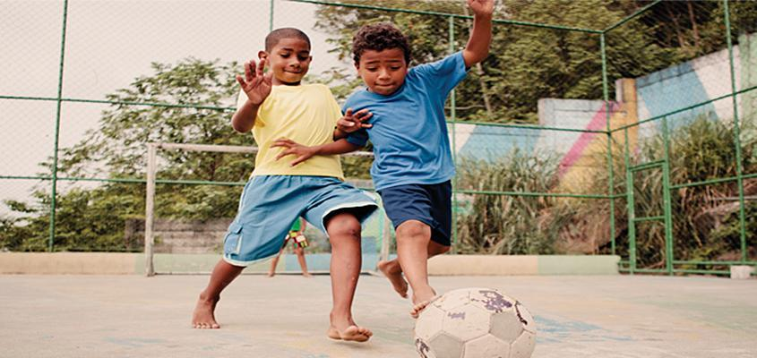 Two young children playing soccer outside.