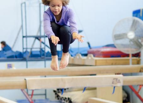 A girl jumping on a balance beam