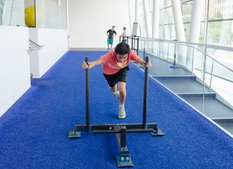 A teenager pushing a training sled