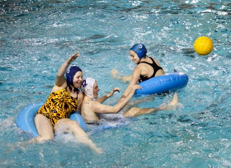 men and women playing innertube Water Polo