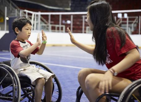A boy and a councellor plays wheelchair basketball