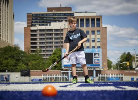 A young boy learns the fundamentals of field hockey