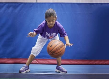A young camper practices dribbling a basketball